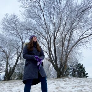 see heather smile, woman, winter, winter coat, purple mittens, winter trees, bare trees, low perspective, snow